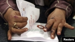 An official counts ballots after polls closed during the final stage of a referendum on Egypt's new constitution in Bani Sweif, about 115 km (71 miles) south of Cairo, December 22, 2012.