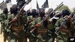 FILE - Al-Shabab fighters march with their guns during military exercises on the outskirts of Mogadishu, Somalia.