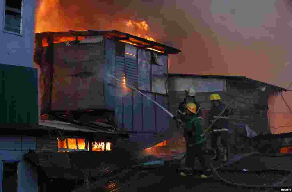 필리핀 마닐라 중심가의 불법 거주지역에 화재가 발생해 소방관들이 불을 끄고 있다.