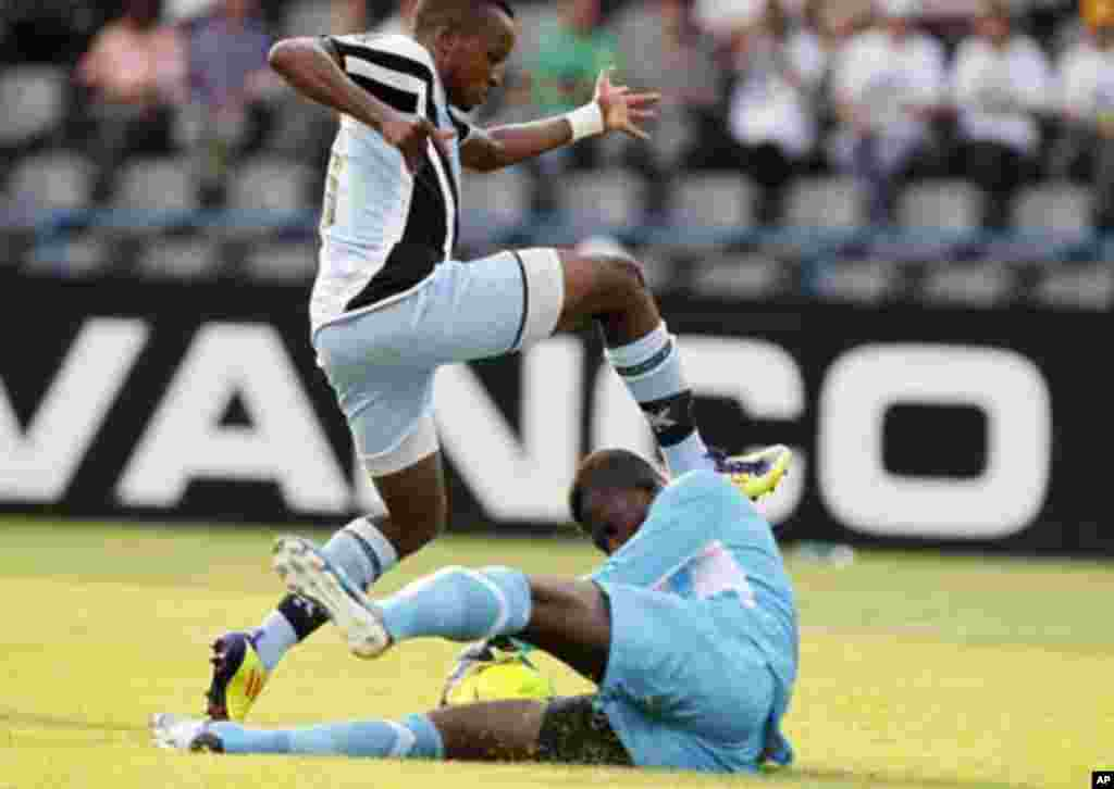 Guinea's goalkeeper Naby Yattara (bottom) makes a save from Botswana's Ofentse Nato during their African Nations Cup Group D soccer match at Franceville Stadium January 28, 2012.