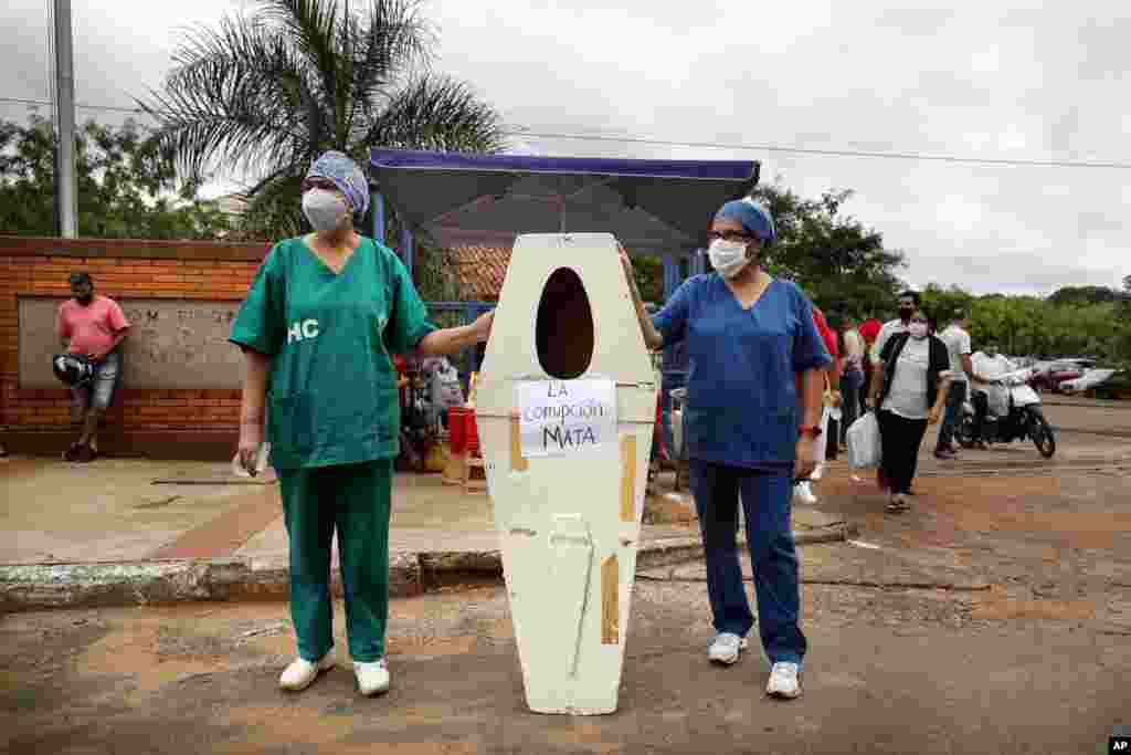 """Nurses who work at the Hospital de Clinicas hold up an empty coffin with the Spanish message """"Corruption kills"""" before the start of a protest demanding more medical supplies, outside their public hospital in San Lorenzo, Paraguay."""