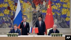 Tổng thống Nga Vladimir Putin (trái) và Chủ tịch Trung Quốc Tập Cận Bình (phải) trong buổi lễ ký kết ở Thượng Hải, Trung Quốc, 21/5/2014.