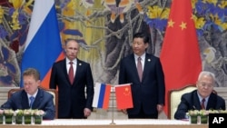 Russia's President Vladimir Putin (Background L) and China's President Xi Jinping (Background R) watch during a signing ceremony in Shanghai, China, May 21, 2014.