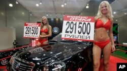 "FILE - Models advertise ""Geely Otaka,"" a car designed in China, during an auto show in Moscow, Russia."