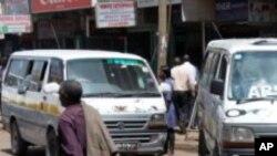 A man walks past two Kenyan minibuses in Nairobi.