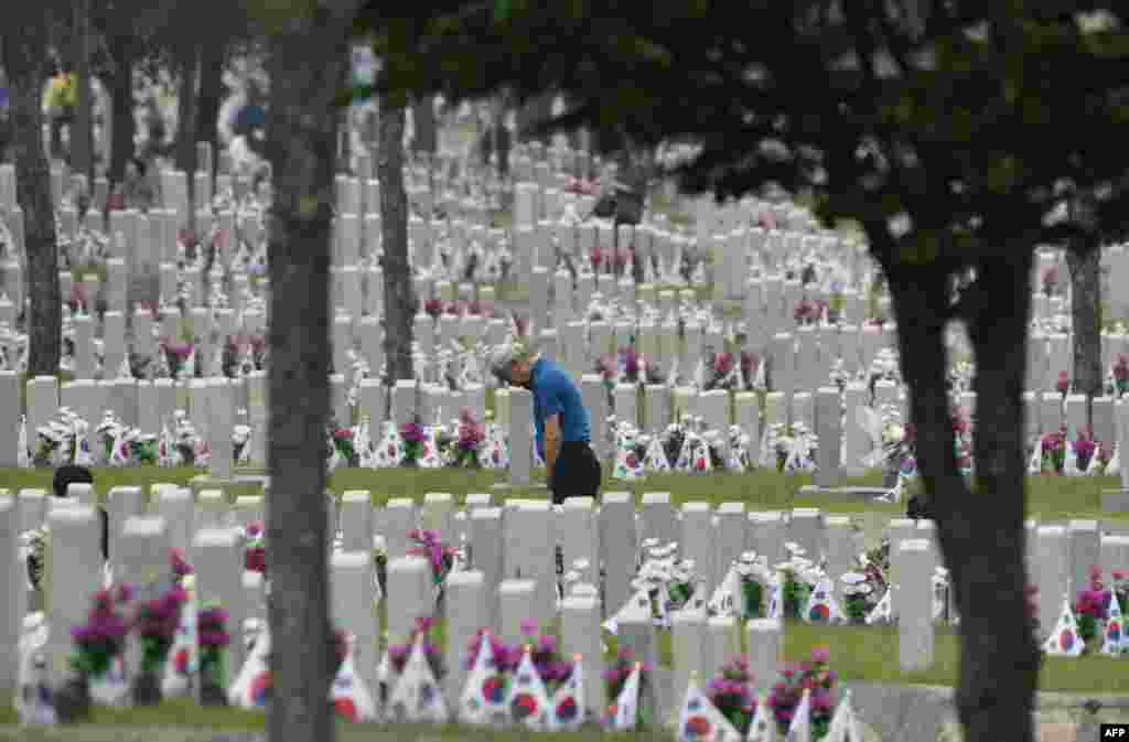 A South Korean man visits the grave of his relative killed in the 1950-53 Korean War, at the National Cemetery in Seoul, on the Korean Memorial Day.