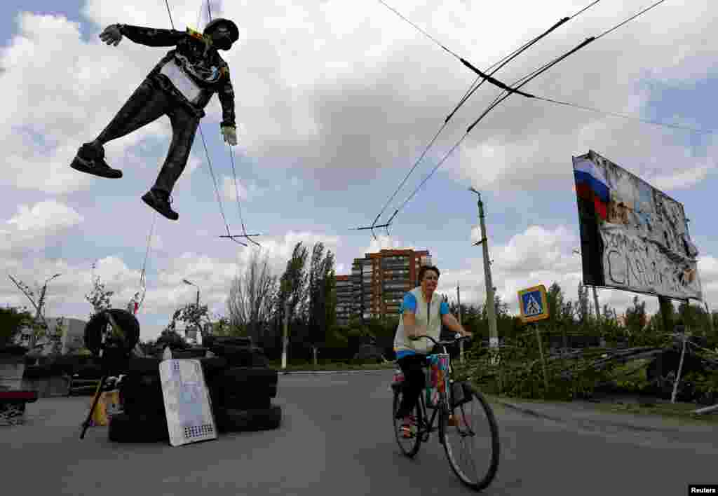 An effigy of a Ukrainian soldier hangs above a pro-Russian checkpoint as a local woman cycles by the entrance of the eastern Ukrainian town of Slovyansk, May 13, 2014.