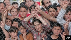 FILE - Migrants stand behind a fence at the Nizip refugee camp in Gaziantep province, southeastern Turkey, April 23, 2016.