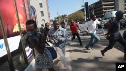 FILE - Protesters disperse in Harare Aug. 24, 2016, after Zimbabwe police fired tear gas, water cannon and gunshots to stop hundreds of youths rallying against the government of President Robert Mugabe.