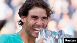 Rafael Nadal dari Spanyol berpose dengan pialanya setelah mengalahkan Juan Martin Del Potro dari Argentina dalam final tunggal putra BNP Paribas Terbuka, Minggu (17/3). (Reuters/Danny Moloshok)