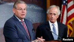 美國參議院外交委員會主席梅嫩德斯(左)3月27日在國會山舉行的記者會上