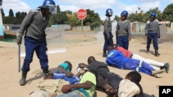 FILE: Armed Zimbabwean police detain rioters in Harare, Monday, July, 4, 2016. Police in Zimbabwes capital fired tear gas and water cannons in an attempt to quell rioting by taxi and mini bus drivers protesting what they describe as police harassment.