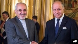 Menteri Luar Negeri Perancis Laurent Fabius (kanan) bersama mitranya dari Iran Jawad Zarif di Paris (5/11). (AP/Benjamin Girette)