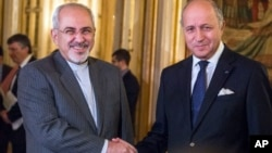 FILE - French foreign minister Laurent Fabius, right, poses for photographers with his Iranian counterpart Jawad Zarif prior to their meeting at the Quai d'Orsay in Paris, France, Nov. 5, 2013.
