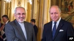 法国外长法比尤斯(右)和伊朗外长扎里夫11月3日在巴黎会晤前握手