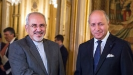 French foreign minister Laurent Fabius, right, poses for photographers with his Iranian counterpart Jawad Zarif prior to their meeting at the Quai d'Orsay in Paris, France, Nov. 5, 2013.