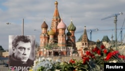 FILE - A portrait of Kremlin critic Boris Nemtsov and flowers are pictured at the site where he was killed on February 27, with St. Basil's Cathedral seen in the background, at the Great Moskvoretsky Bridge in central Moscow, March 6, 2015.