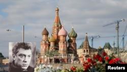 រូបភាពលោក Boris Nemtsov និងកម្រងផ្កានៅកន្លែងដែលលោកត្រូវបានសម្លាប់កាលពីថ្ងៃទី២៧ ខែកុម្ភៈ។ មនុស្ស២នាក់ត្រូវចាប់ខ្លួនក្នុងរឿងឃាតកម្មលោក។