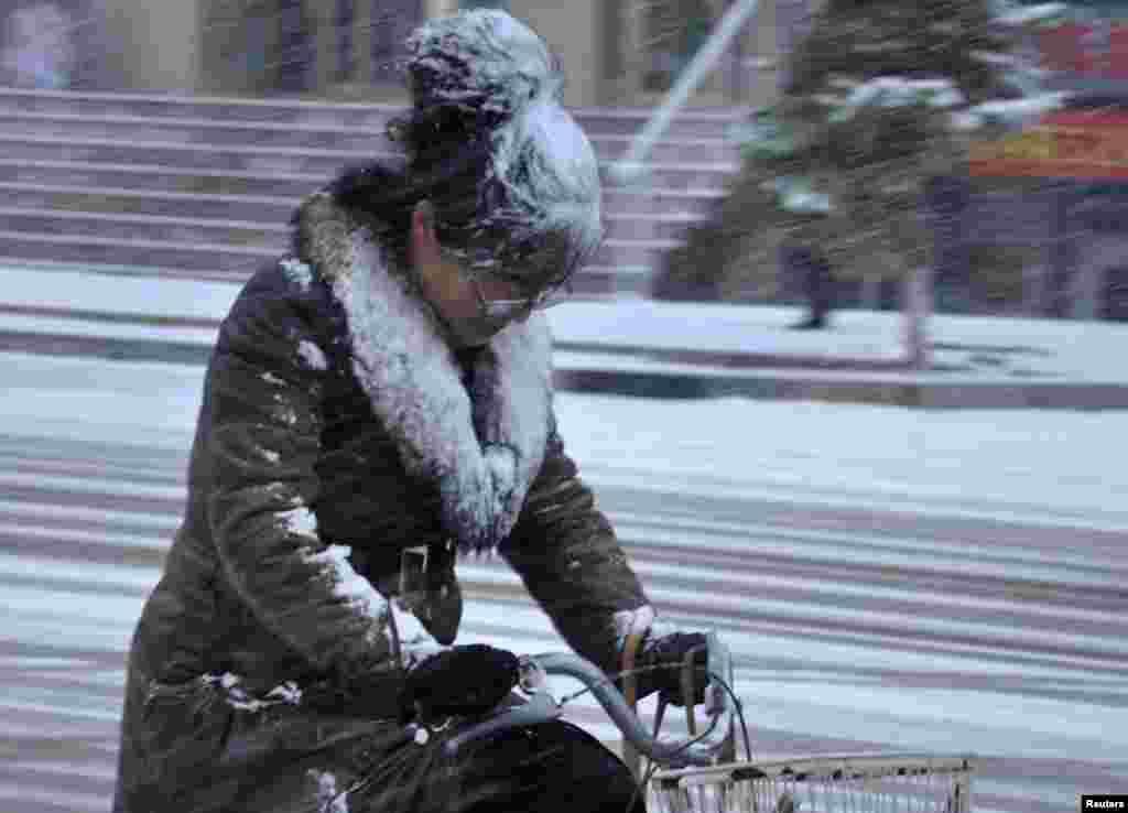 چین کے شمالی اِنر منگولیا خودمختار خطے میں سائیکل پر سوار ایک خاتون تیز ہوا اور برف باری کی مخالف سمت سفر کر رہی ہیں۔