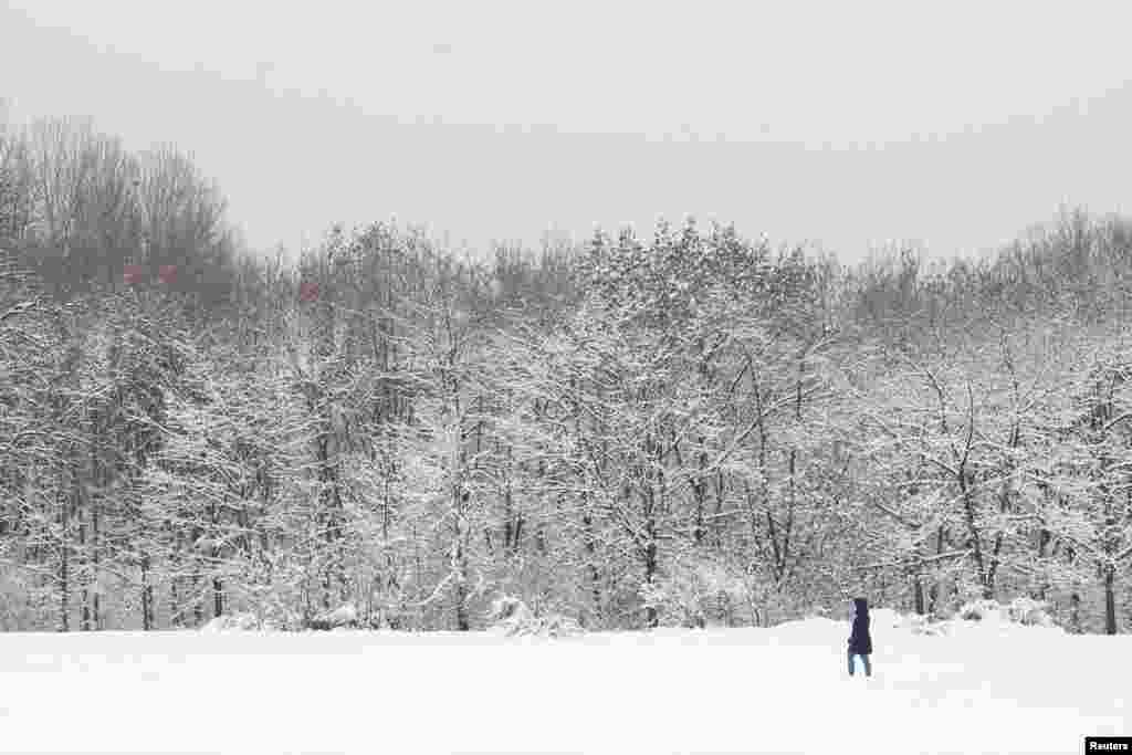A woman walks in a park during snowfall in Sofia, Bulgaria.