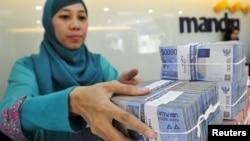 Kasir di kantor cabang Bank Mandiri sedang menghitung mata uang Rupiah di Jakarta 20 Juli 2015. (Foto: Antara via Reuters)