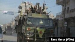 Di vê fotoya arşîvê de şervanên YPG serkeftina xwe pîroz dikin