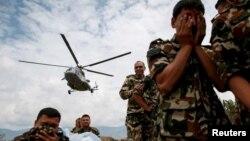 Soldados nepaleses se cubren mientras un helicóptero de la India evacúa personas heridas en Sindhupalchowk, luego del terremoto del sábado.
