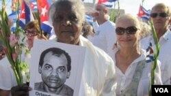 En Miami, una dama de blanco sostiene una foto de Orlando Zapata Tamayo, el disidente que murió tras una huelga de hambre de 85 dias, y que motivó un mayor diálogo según la Iglesia Católica.