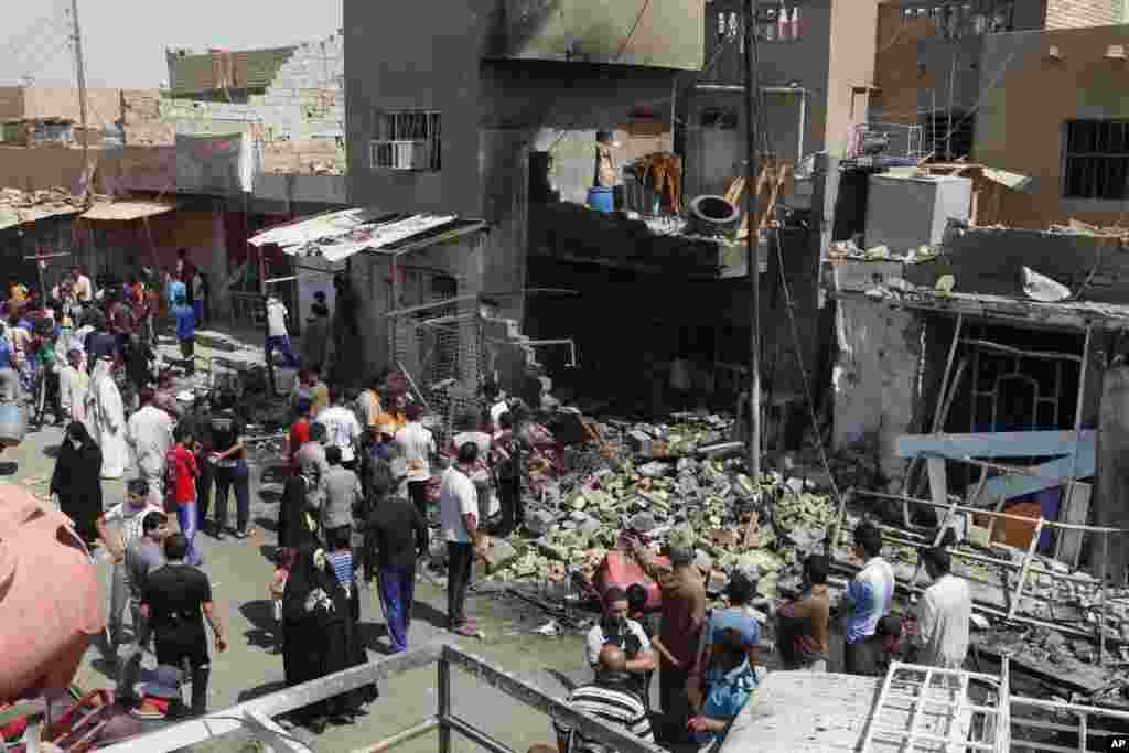 People inspect the scene of a bomb attack in Madain, southeast of Baghdad, Iraq, July 23, 2012.