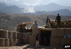 ARCHIVO - Policías afganos miran hacia el horizonte donde una columna de humo se levanta luego de un ataque a posiciones de militantes del Estado Islámico en un punto de control en la oriental provincia de Nangarhar. Julio 7, 2018.
