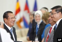 Cambodian Prime Minister Hun Sen, left, smiles as he greets international observers for the July 29 general election, during a welcome meeting at Peace Palace, in Phnom Penh, Cambodia, July 28, 2018. Few of the observers expressed any reservations after the poll.