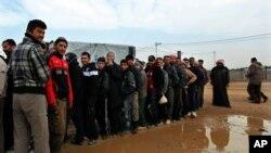 Para pengungsi Suriah di kamp Zaatari, Yordania antri menunggu pembagian kasur, selimut dan keperluan lainnya (28/1).
