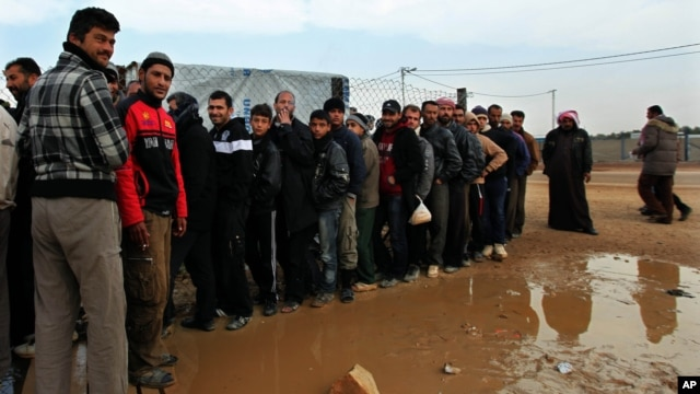 Newly arrived Syrian refugees wait their turn to receive mattresses, blankets and other supplies, and to be assigned to tents, at the Zaatari Syrian refugees camp in Mafraq, near the Syrian border with Jordan, Jan. 28, 2013.