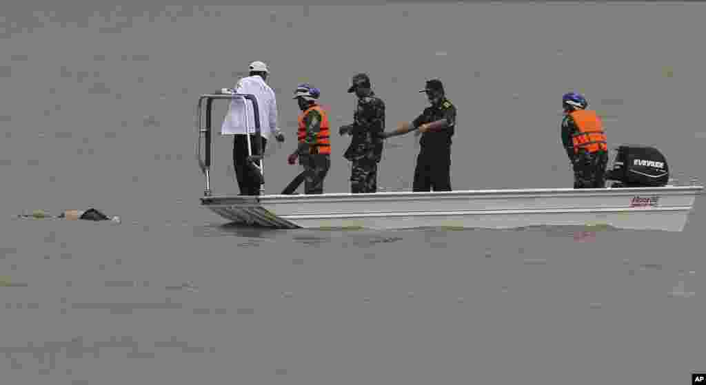 Rescue workers recover the body of a plane crash victim in the Mekong River in Pakse, Laos, Oct. 18, 2013.