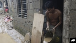 Ramon Fabros pours muddy water out of his house after floodwaters brought by Typhoon Nesat receded, September 28, 2011 in suburban San Mateo, eastern of Manila, Philippines.