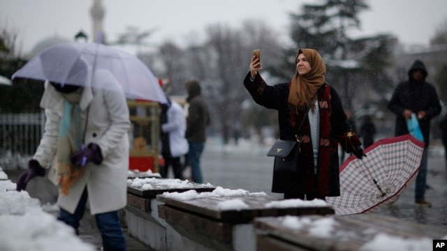 A visitor takes a picture in the historic Sultanahmet district in Istanbul, Jan. 18, 2016. Heavy snowfall has swept northwestern Turkey, grounding hundreds of flights, disrupting ground transport and closing schools in Istanbul.