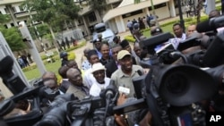 Nigeria's president Goodluck Jonathan, center right, fields questions from journalists as he leaves U.N. headquarters, where a day earlier a suicide bomber crashed through an exit gate and detonated a car full of explosives, in Abuja, Nigeria.