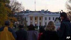 Curiosos se acercan a la cerca de la Casa Blanca luego que el Servicio Secreto arrestara a un hombre que la saltó.
