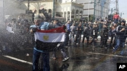 A protester holds an Egyptian flag as he stands in front of water canons during clashes in Cairo, Jan 28, 2011