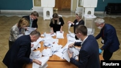 Members of a local election commission count ballots at a polling station inside Kazansky railway terminal after polls closed during a three-day long parliamentary election in Moscow, Russia, Sept. 19, 2021.