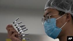 一位工作人員在檢查中國盛產的新冠疫苗。(美聯社2020年9月25日)
