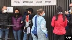 Warga Australia antri untuk melakukan tes Covid-19 di sebuah rumah sakit di kota Melbourne (16/7). Melbourne memberlakukan kewajiban memakai masker.
