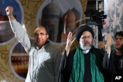 Iranian presidential candidate cleric Ebrahim Raisi, right, waves to his supporters while he is accompanied by Tehran Mayor Mohammad Bagher Qalibaf upon arrival at a campaign rally for the May 19 election at Imam Khomeini grand mosque in Tehran.