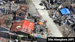 A house with the writings on the roof saying that food and water are needed is seen from a Philippine Air Force helicopter.