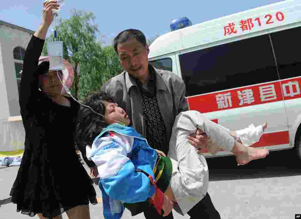 Một người đàn ông bế một người đàn bà bị thương đến một trạm xá tạm để được chữa trị sau trận động đất tại huyện Lộ Sơn, Nhã Yên, thuộc tỉnh Tứ Xuyên, tây nam Trung Quốc, ngày 20 tháng 4, 2013.