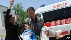 2013年4月20日星期六,中国四川省雅安市芦山县发生里氏7级强烈地震。一名男子抱着一名受伤的女孩,旁边一名妇女帮着拿点滴,前往临时救护站。