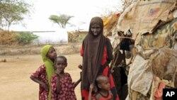 肯尼亚的难民营已经不堪负荷。图为一名索马里女难民和孩子们在两国边境处的临时庇护处