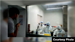 Cambodian medical personnel dressed in protective gear perform coronavirus testing in a lab. (Courtesy of Cambodia's Communicable Disease Control Department)