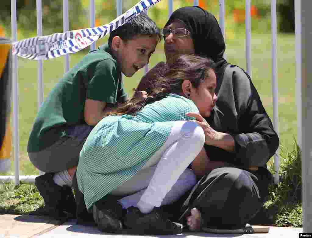A woman hugs her children near where a vehicle crashed into a primary school classroom in the Sydney suburb of Greenacre in Australia.