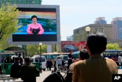 North Koreans watch as their country's most famous newscaster announces leader Kim Jong Un's proposal to suspend nuclear tests and long-range missile launches on a giant screen on Pyongyang's newly built Mirae Scientists' Street.